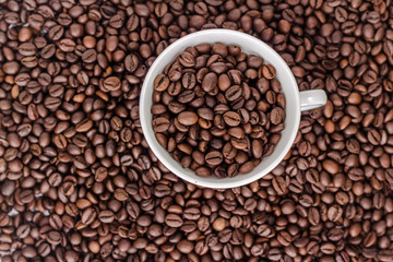Cup with coffee beans on background of coffee bean, top view