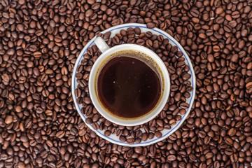 mug of black coffee on background of coffee bean