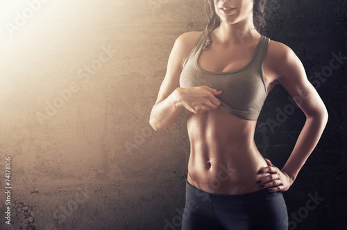 Dysponowana młoda kobieta pokazuje jej abs