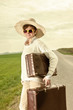 Woman running on the road and wearing holiday suitcase