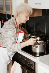 Elderly woman in cooking in the kitchen