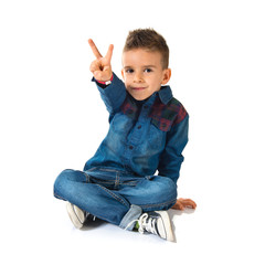Kid doing victory gesture over white background