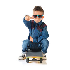 Kid playing with skate board with thumb up