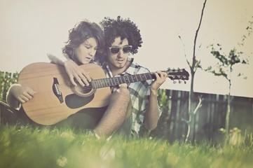 Boy teaches girl to play guitar