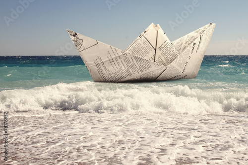 paper boat floating in a sea © ronstik