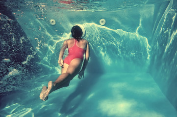 Girl swimming underwater in pool.
