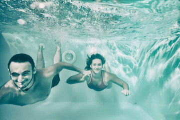 Girl and boy swimming underwater in pool.