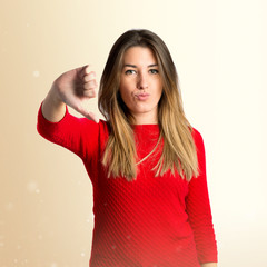 Young girl doing a bad signal over white background