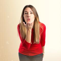 Pretty girl sending kiss over white background