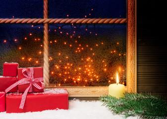 Geschenke und Kerze am Fenster
