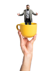 young businessman with gas mask inside cup of coffee