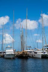 Old Teak Sailboat Among Modern White Yachts