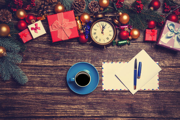 Hot coffee with letter near christmas gifts on wooden table.