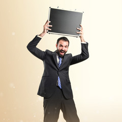 Young businessman with his briefcase over white background