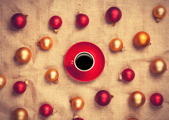 Hot coffee and christmas balls on jute background.
