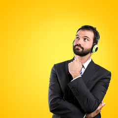 Young businessman listening music over yellow background