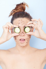 Woman with a facial scrub an cucumber