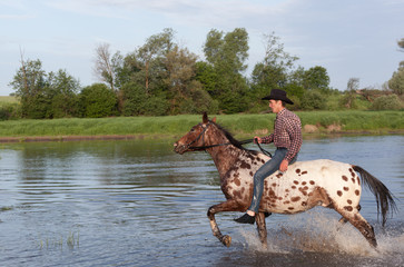 Young rider gallops on a horse down the river