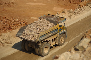 huge trucks work in a quarry mining