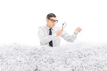 Angry man examining a pile of shredded paper