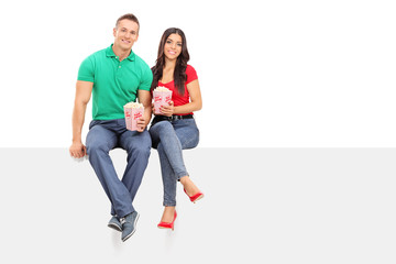 Couple holding popcorn seated on a blank panel