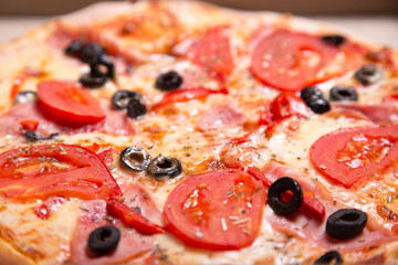 Close-up shot of Italian pizza with ham, tomatoes and olives