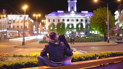 The lovers sit by night city square