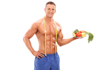 Shirtless athlete holding a plate with vegetables