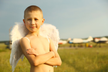 boy with angel wings on the airfield