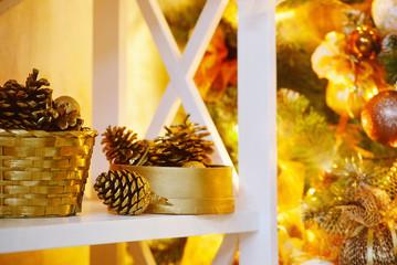 Shelf with golden decoration items near lighting Christams tree