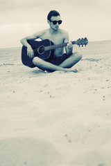 Boy playing guitar on the beach