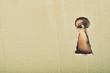 Leinwanddruck Bild - Eye looking through a conceptual keyhole on cardboard, close up