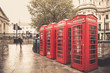 Vintage style  red telephone booths on rainy street in London - 74186555