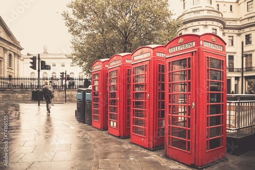 London Vintage style red telephone booths on rainy street in London