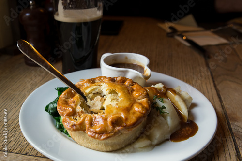 Traditional chicken pot pie in authentic UK pub setting - 74186569