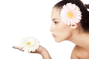 young beautiful woman enjoying the scent of the flower gerbera