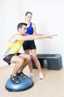 Weiblicher Trainer hilft bei Kniebeuge