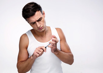 Handsome man doing manicure over gray background
