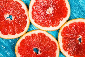 Red grapefruit slices on blue wooden background