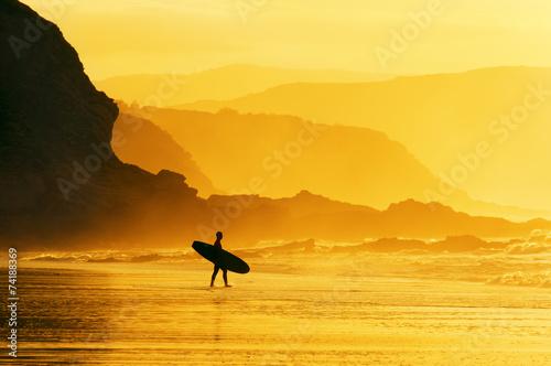 surfer entering water at misty sunset - 74188369