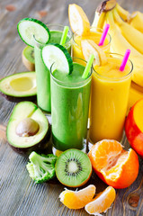 Green and yellow smoothie in glasses with avocado, kiwi, mango