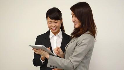タブレット端末を操作する二人の女性