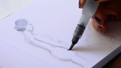 Pencil of sketcher painting in a book
