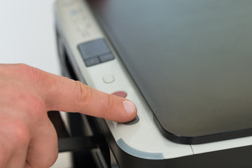 Businessman's Finger Pressing Button Of Photocopy Machine