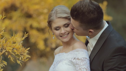 Groom with bow tie gently kisses the young bride and hugging her