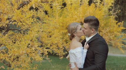 Lovely bride passionately kisses her young handsome groom