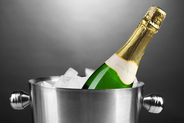 Bottle of champagne in bucket with ice, on grey background