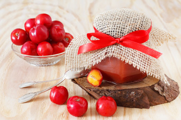 Jam, confiture of Malpighia glabra (red acerola) in jar and fres