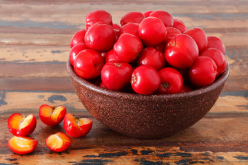Malpighia glabra (red acerola), tropical fruit  on wooden table