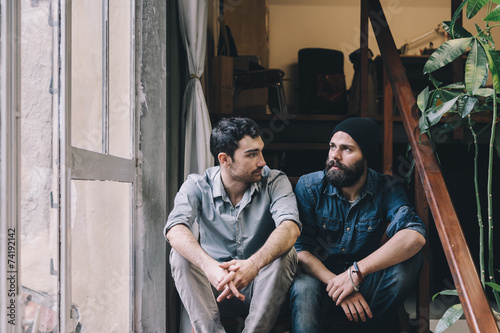 Couple of young men talking on the stairs of an office - 74192142